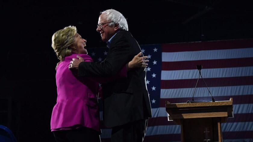 La candidata presidencial demócrata, Hillary Clinton, y el senador de Vermont Bernie Sanders, se abrazan durante un mitin de campaña en Raleigh, Carolina del Norte, el jueves.