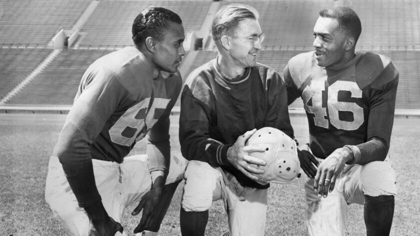 Woody Strode, left, and Kenny Washington, right, listen to Los Angeles Rams coach Adam Walsh in a publicity photo taken at the Memorial Coliseum on Sep. 7, 1946.