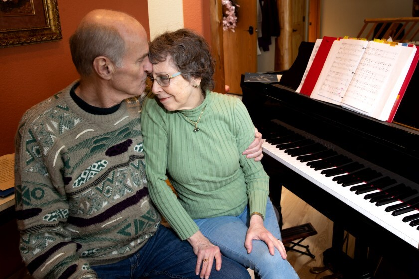 Skagit Valley Chorale members Mark Backlund and his wife, Ruth, embrace in their Anacortes, Wash., home March 27 during their convalescence from COVID-19, which claimed the lives of two fellow choir members within days of a rehearsal.