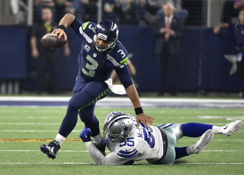 Seattle Seahawks' Russell Wilson (3) breaks away from a tackle-attempt by Dallas Cowboys' Rolando McClain (55) in the second half of an NFL football game Sunday, Nov. 1, 2015, in Arlington, Texas. (AP Photo/Michael Ainsworth)