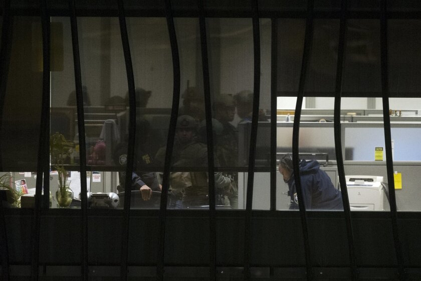Police search a building on the U.S. Census  Bureau headquarters campus for an armed man who, according to a fire official, shot a security guard at a gate to the facility in Suitland, Md., Thursday, April 9, 2015. (AP Photo/Cliff Owen)