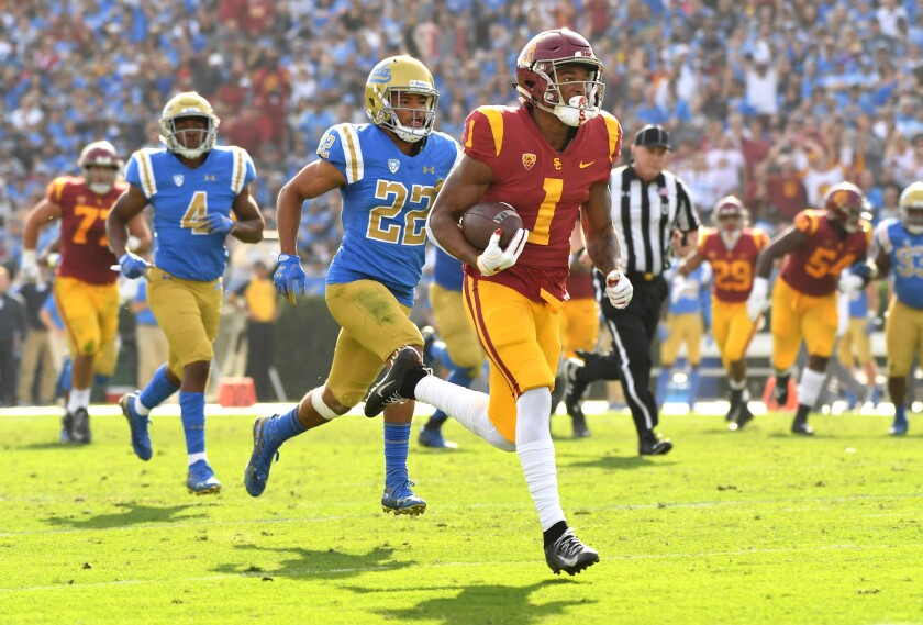 USC receiver Velus Jones Jr. sprints to the end zone for a touchdown as UCLA defensive back Nate Meadors gives chase in the second quarter at the Rose Bowl on Nov. 17, 2018.