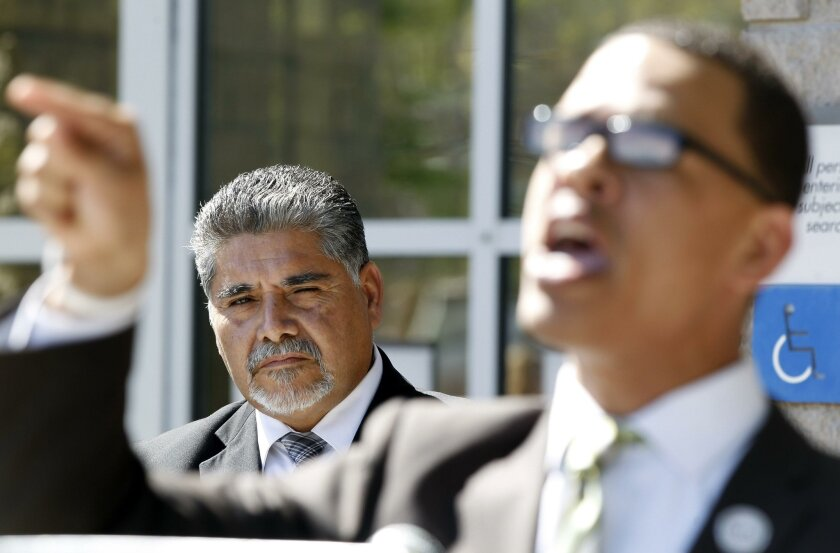 The Rev. Shane Harris, of the National Action Network, speaks in support of Escondido school district Trustee Jose Fragozo (background) during a news conference Friday outside the Vista Courthouse.