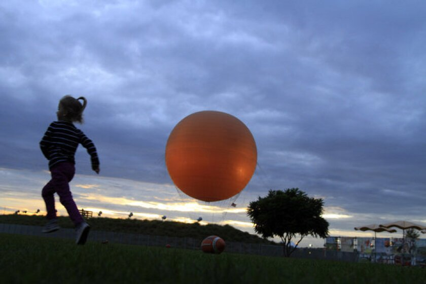 A child plays in Orange County's Great Park, with the park's balloon in the background. Irvine leaders will consider whether to issue subpoenas to help auditors continue their investigation into the financial management of the park.