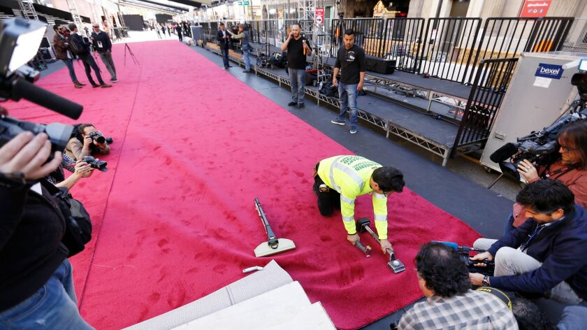 Carpet installer Rudy Morales positions the red carpet in front of the Dolby Theatre in Hollywood in advance of the 89th Academy Awards on Sunday.
