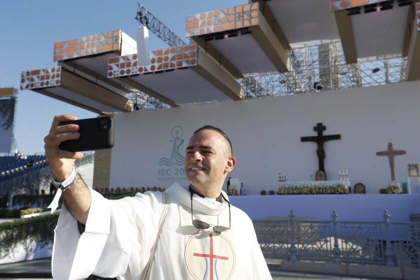 Un sacerdote se toma una foto con el altar de fondo donde el papa Francisco ofreció una misa