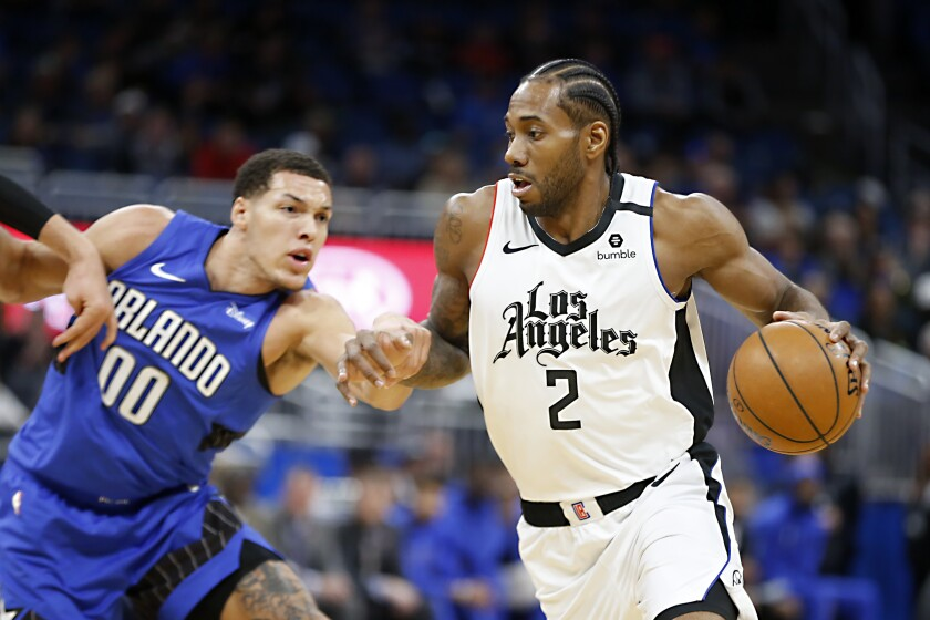 Kawhi Leonard drives past Orlando Magic forward Aaron Gordon in a game last month.