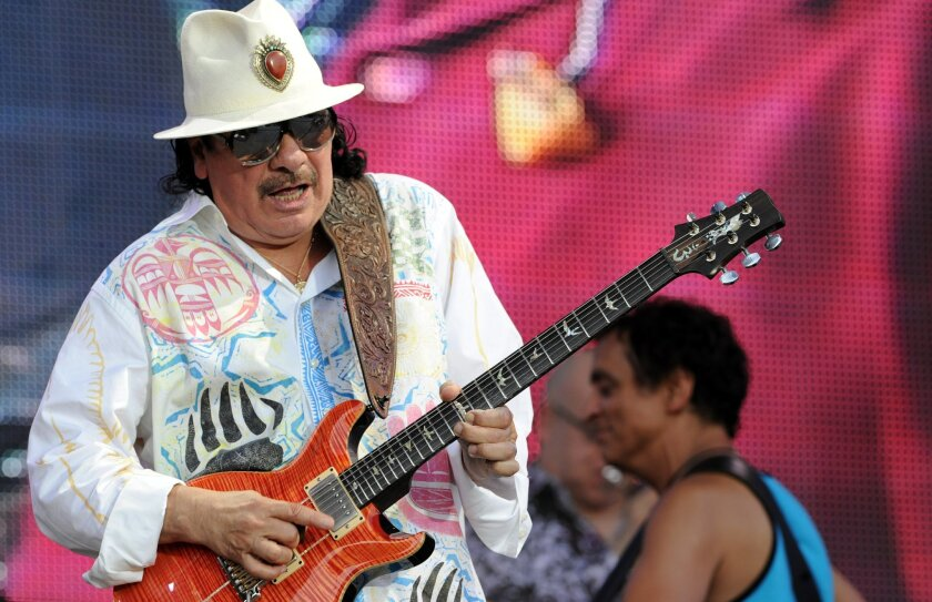 US guitarist and singer Carlos Santana performs on July 21, 2013 during the Vieilles Charrues music Festival in Carhaix-Plouguer, western of France. AFP PHOTO FRED TANNEAU        (Photo credit should read FRED TANNEAU/AFP/Getty Images)
