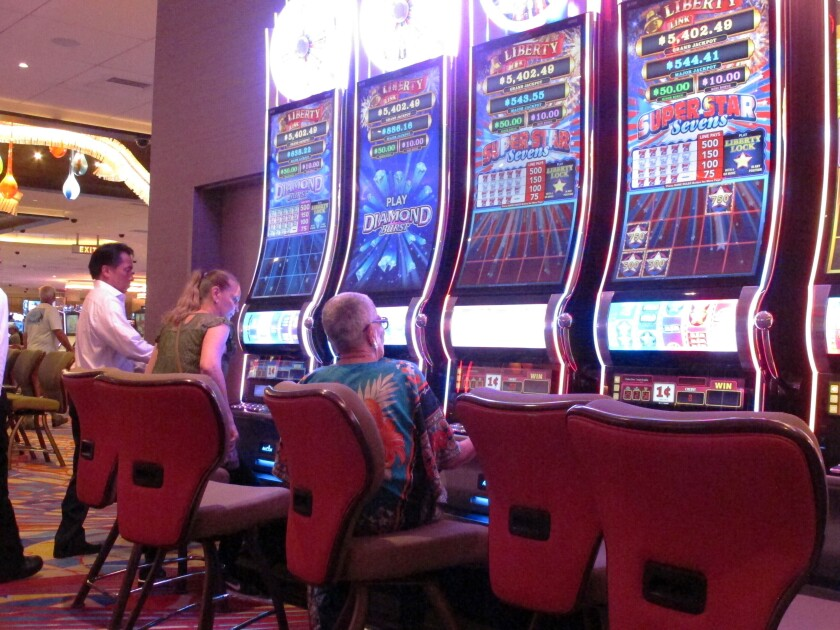 This June 20, 2019 photo shows gamblers playing slot machines at the Hard Rock casino in Atlantic City, N.J. Figures released by state gambling regulators on Wednesday, Feb. 12, 2020, show New Jersey's gambling industry won more than $300 million in January 2020 on casino games, internet gambling and sports betting, an increase of nearly 31% from January 2019. (AP Photo/Wayne Parry)