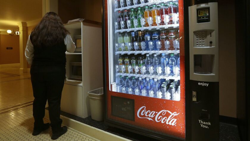 A Coca-Cola vending machine sits in the basement of the state Capitol as members of the Legislature debate a ban on local soda taxes.