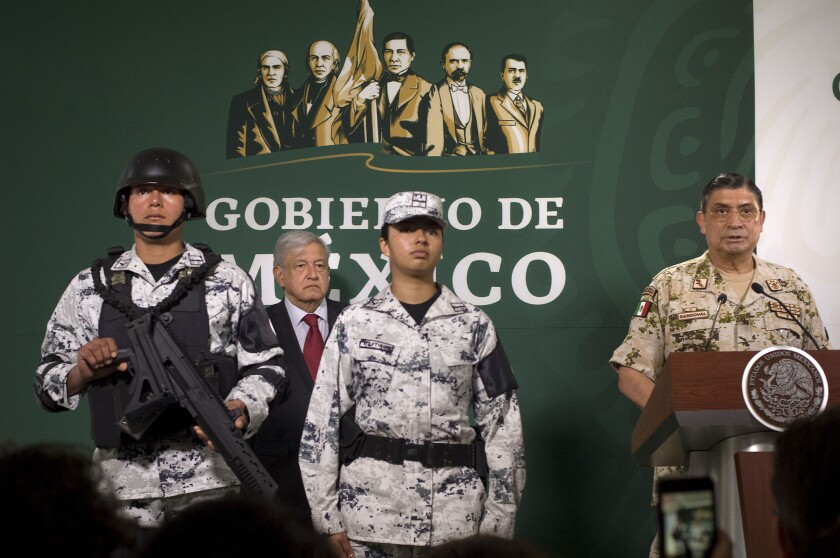 Mexican Secretary of Defense, Luis Sandoval, right, talks about a new Mexican National Guard (Guardia Nacional) during a press conference with Mexican president, Andres Manuel Lopez Obrador, background, at a military base in Tijuana, Mexico, on March 27, 2019. Photo - David Maung