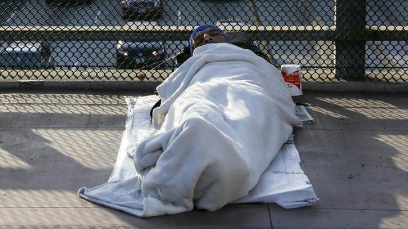 A homeless man sleeps on a bridge over Main Street in downtown Los Angeles.