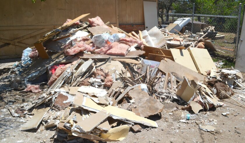 Drywall, insulation and other items are piled outside a home near Ninth Street and Ashley Road that was flooded during last weekend's storm.