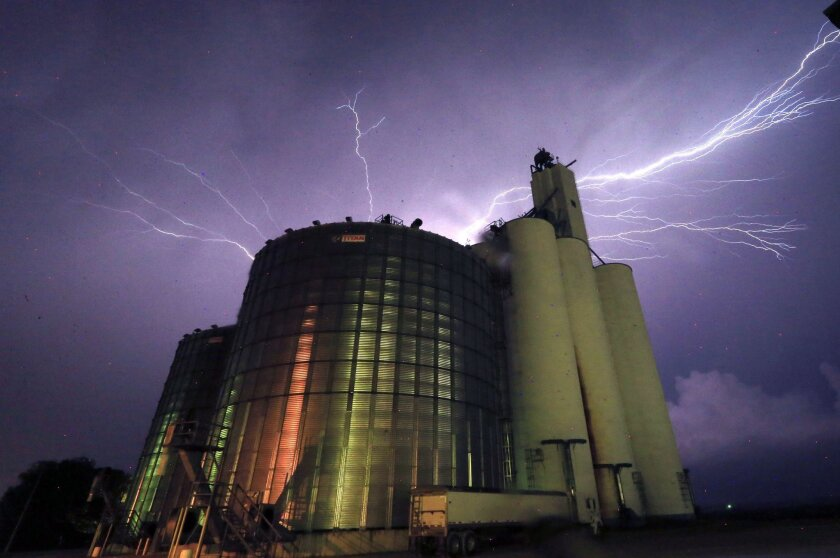Lightning from a severe storm fills the sky behind a grain elevator in Belvue, Kan., Wednesday, May 25, 2016. The storm produced tornadoes near Chapman, Kan. (AP Photo/Orlin Wagner)