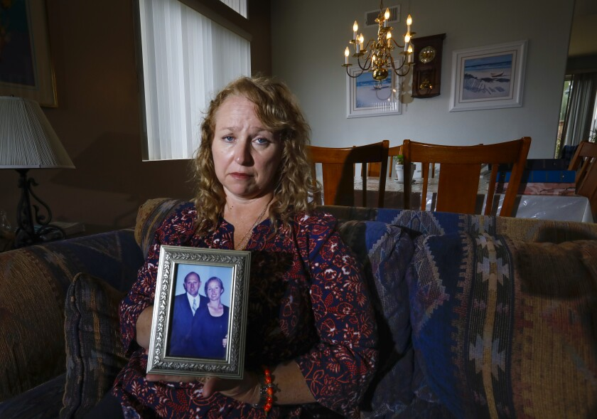 Theresa Sturkie holds a photo of she and her husband of 21 years, John Sturkie, at her home on May 21, 2019 in Oceanside