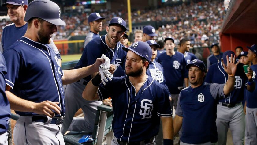 San Diego Padres' Jordan Lyles, left, is welcomed in the dugout, after scoring against the Arizona D