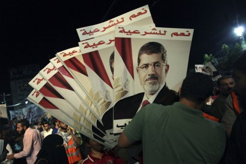 "A supporter of Egypt's ousted President Mohammed Morsi holds his posters with Arabic writing which reads "" Yes for legality,"" during a protest outside Rabaah al-Adawiya mosque, where protesters have installed a camp and hold daily rallies at Nasr City in Cairo, Egypt, Tuesday, Aug. 6, 2013. (AP Photo/Khalil Hamra)"