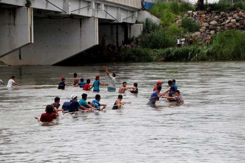 Decenas de migrantes hondureños cruzan a pie el río Suchiate, que separa a Guatemala de México. EFE
