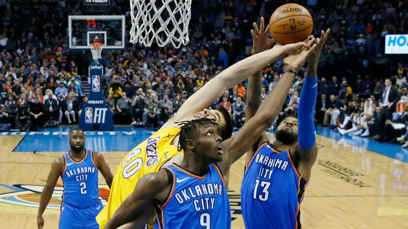 The Lakers' Ivica Zubac vies for a rebound against Oklahoma City's Jerami Grant (9) and Paul George on Jan. 17.