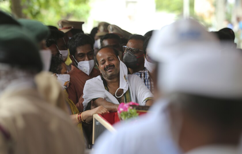 """B. Upender weeps by the coffin of his son Colonel B. Santosh Babu in Suryapet, about 140 kilometers from Hyderabad, India, Thursday, June 18, 2020. Babu was among the twenty Indian troops who were killed in the clash Monday night that was the deadliest conflict between the sides in 45 years. India on Thursday cautioned China against making """"exaggerated and untenable claims"""" to the Galvan Valley area even as both nations tried to end a standoff in the high Himalayan region where their armies engaged in a deadly clash. (AP Photo/Mahesh Kumar A.)"""
