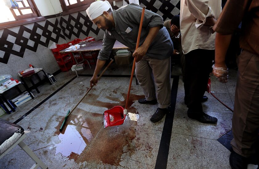 A man cleans blood from a makeshift hospital after dozens were killed in clashes between supporters of Egypt's ousted president, Mohamed Morsi, and security forces in Cairo.
