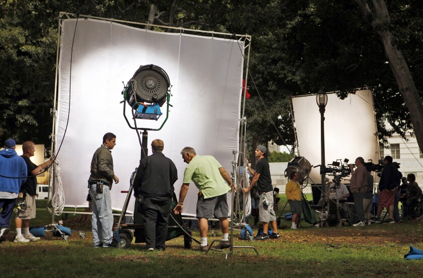 A film crew sets up lights and cameras for shooting a scene.