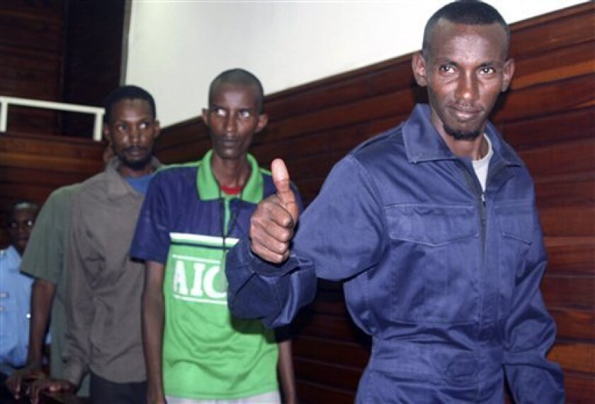 One of the seven suspected Somali pirates gives a thumbs up as he arrives at the Mombasa Law courts Monday Sept. 6, 2010, in Kenya. The seven Somali suspects were each jailed for five years after they were found guilty of piracy but were given a chance to appeal. The seven Somali suspects were arrested by a German Naval Frigate supply ship MV Spessart as they attempted to hijack the ship on May last year while armed with offensive weapons including five AK47s, two pistols, one rocket propelled grenade launcher and a knife.(AP Photo).