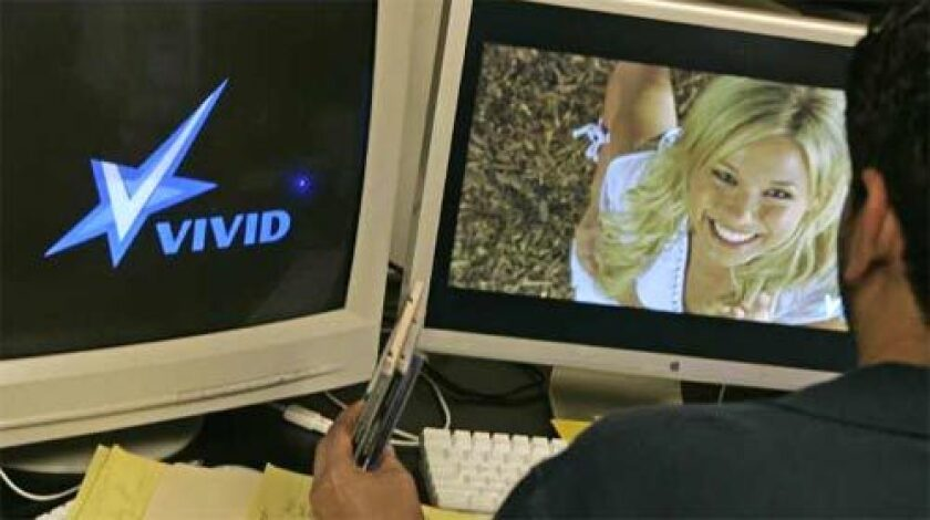DUAL ROLE: An editor works this year at Vivid in Los Angeles. The Internet has helped porn companies boost sales, but the proliferation of unauthorized free clips online has undercut them.