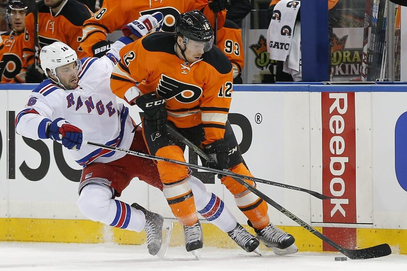 Philadelphia Flyers left wing Michael Raffl (12) maintains control of the puck against New York Rangers center Derick Brassard (16) during the first period of an NHL hockey game, Sunday, Feb. 14, 2016, in New York. (AP Photo/Julie Jacobson)