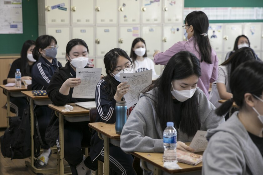 South Korean students in masks work at their desks.