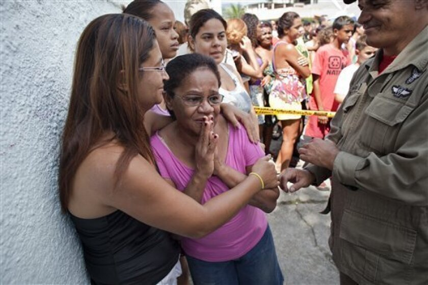 A police officer, right, stands by women gathered outside a school after a shooting at the school in Rio de Janeiro, Brazil, Thursday, April 7, 2011. Brazilian authorities say that a gunman opened fire in an elementary school in Rio de Janeiro and at least 13 people are dead, including the gunman, and at least 20 people are wounded. (AP Photo/Victor R. Caivano)