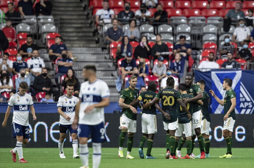 Portland Timbers players celebrate after a Vancouver Whitecaps own goal during the second half of an MLS soccer match Friday, Sept. 10, 2021, in Vancouver, British Columbia. (Darryl Dyck/The Canadian Press via AP)