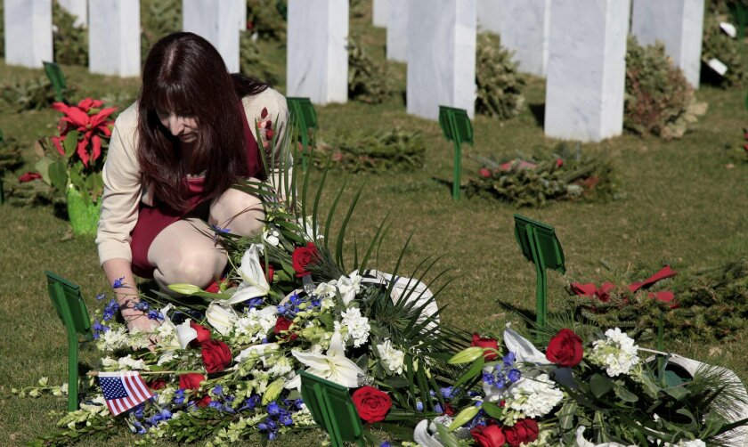The reburial of Edwin Ware took place at Miramar's National Cemetary. Ware's great grand-daughter, Sandra Ellis, knelt over to pay respects to her grandfather who was a civil war veteran. U-T Photo by Christian Rodas
