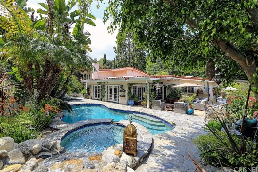 The gated half-acre property holds a 1960s home and an entertainer's backyard with a waterfall-fed pool and spa.