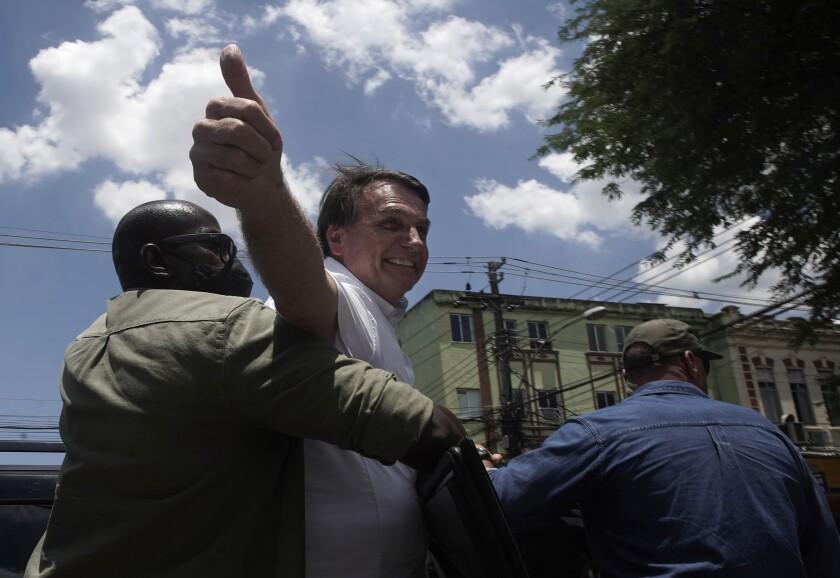 Brazilian President Jair Bolsonaro greets supporters after voting during municipal runoff elections in Rio de Janeiro.