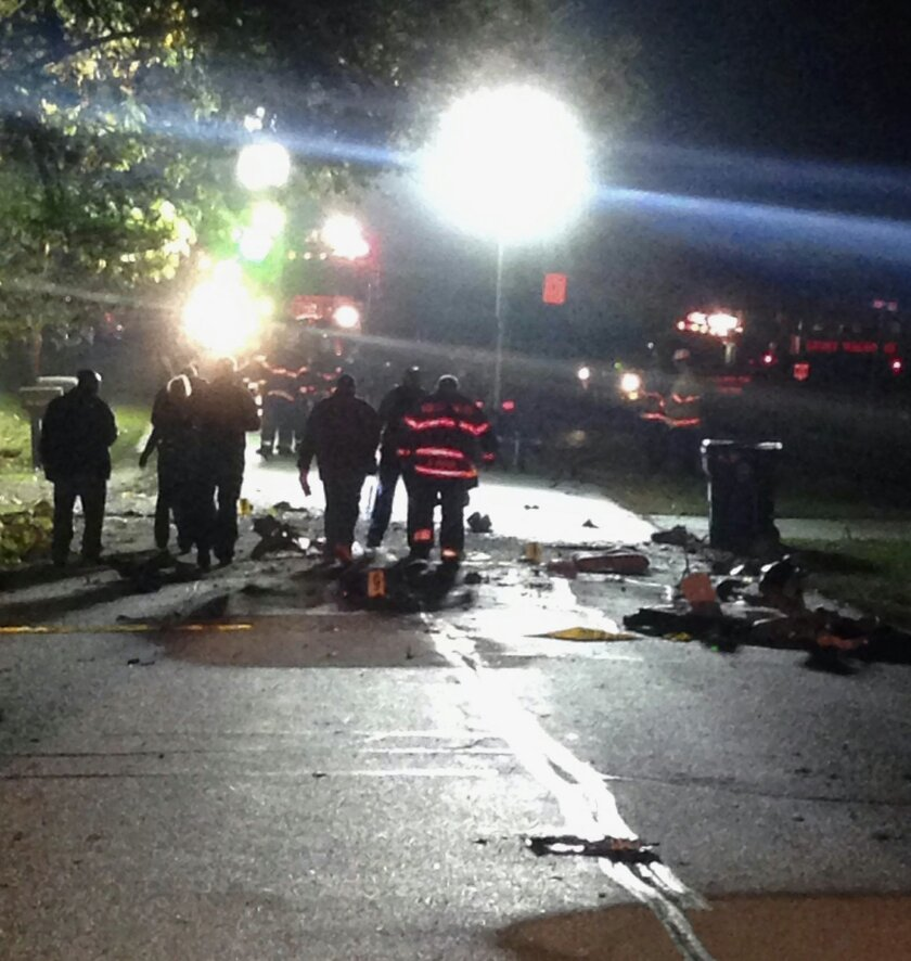 In this Sunday, Oct. 12, 2014 photo provided by Fernanda Villegas, emergency personnel work the scene of a small plane crash in the Chicago suburb of Palos Hills, Ill. Three people aboard the twin-engine Beechcraft Baron were killed in the crash late Sunday night, shortly after takeoff from Chicago Midway Airport en route to Lawrence, Kan. (AP Photo/Courtesy of Fernanda Villegas)