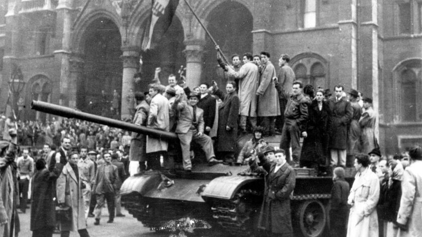 Hungarian rebels wave their red, white and green national flag from a tank captured in Budapest's main square during the revolution of 1956.