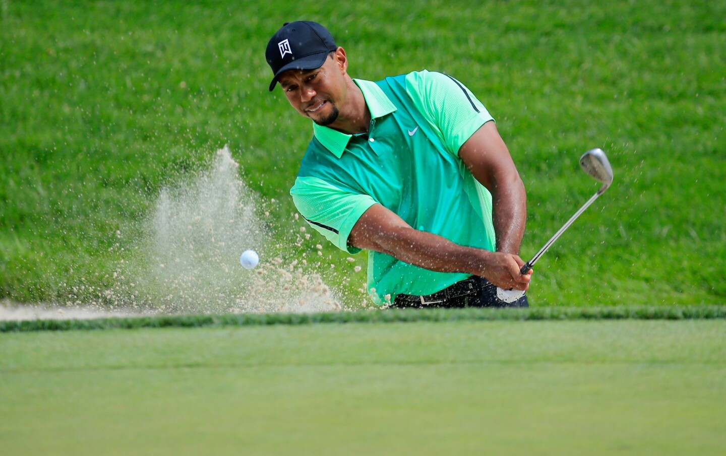 Tiger Woods hits out of a bunker during the first round of the Quicken Loans National.