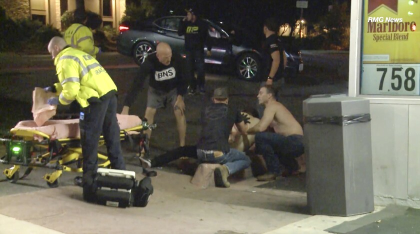 """FILE - In this Wednesday evening, Nov. 7, 2018 file image taken from video a victim is treated near the scene of a shooting, in Thousand Oaks, Calif. A hooded gunman dressed entirely in black opened fire on a crowd at a country dance bar holding a weekly """"college night"""" in Southern California, killing multiple people and sending hundreds fleeing. The 12 people killed in a mass shooting and gun battle at the Southern California country-western bar a year ago have been remembered in a public park memorial called The Healing Garden. The garden was to be dedicated Thursday, Nov, 7. (RMG News via AP, File)"""