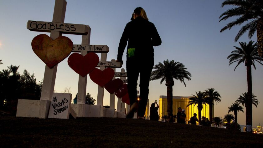 Carol-Ann Seitzinger, 62, of Las Vegas runs her hand over the top of each wooden crosses bearing the names of those killed during the mass shooting.