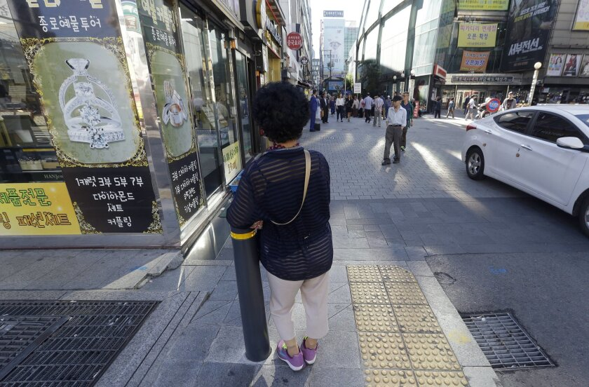 """In this Sept. 17, 2015 photo, an elderly woman stands at a small, bustling plaza in front of the Piccadilly theater in Seoul, South Korea. It's a place where elderly prostitutes openly solicit customers for sex in nearby motels. They are dubbed """"Bacchus ladies"""" after the popular energy drink that they have traditionally sold.(AP Photo/Ahn Young-joon)"""