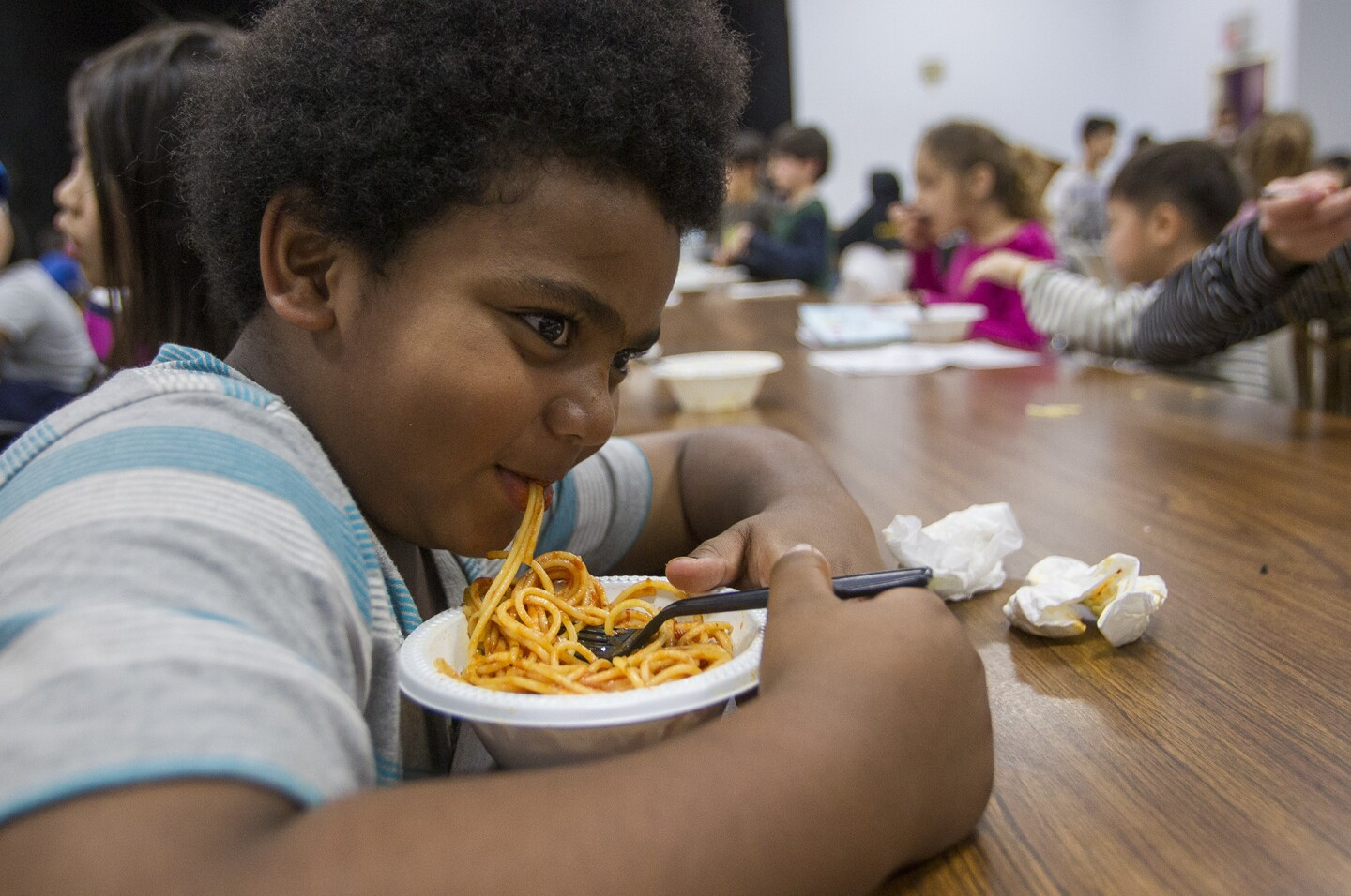 Jeremia Williams, 7, eat a pasta dinner prepared by chef Bruno Serato, of Caterina's Club at the Harbor Boys & Girls Club in Irvine on Wednesday.