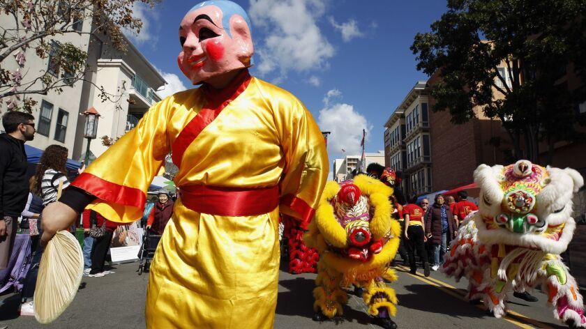 Brian Quach, wearing a Buddha mask and costume, and fellow members of the San Diego Lucky Lion Dancers move down Third Avenue Saturday, launching the 37th Annual San Diego Chinese New Year Fair in downtown San Diego.