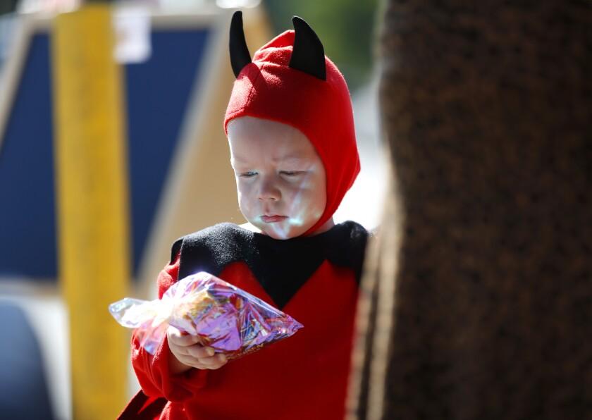 Lux Seacrest, 22 meses, sostiene una bolsa de caramelos en un evento de distribución de dulces