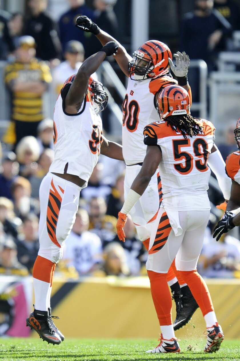 Cincinnati Bengals defensive ends Michael Johnson (90) and Wallace Gilberry (95) celebrate beside outside linebacker Emmanuel Lamur (59) after sacking Pittsburgh Steelers quarterback Ben Roethlisberger in the second quarter of an NFL football game Sunday, Nov. 1, 2015, in Pittsburgh. The Bengals wo