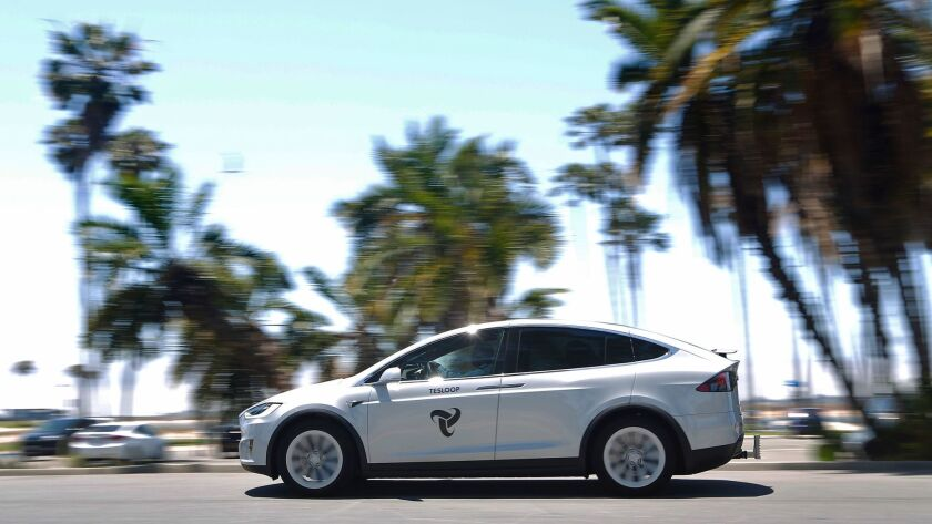 A Tesloop car drives near Mission Bay. The car riding offers service between cities such as San Dieg