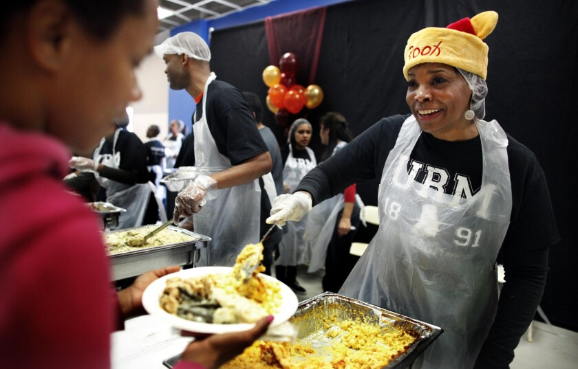 Volunteer Monica Smith serves up a Thanksgiving meal at the Union Rescue Mission in Los Angeles last year.