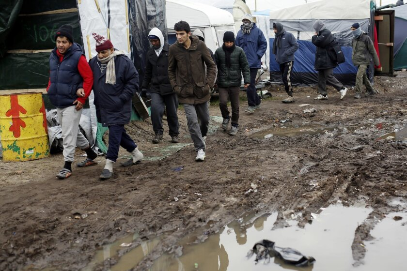 Migrants walk through a makeshift camp set outside Calais, France, Tuesday Feb. 23, 2016. People fleeing conflict and poverty in Africa, the Mideast and Asia are facing an evening deadline to move out of the camp in the French port of Calais that has become a flashpoint in Europe's migrant crisis. (AP Photo/Jerome Delay)