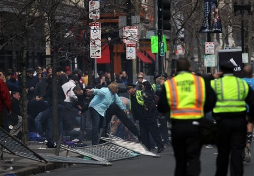 In this photo provided by The Daily Free Press and Kenshin Okubo, people react to an explosion at the 2013 Boston Marathon in Boston, Monday, April 15, 2013. Two explosions shattered the euphoria of the Boston Marathon finish line on Monday, sending authorities out on the course to carry off the in