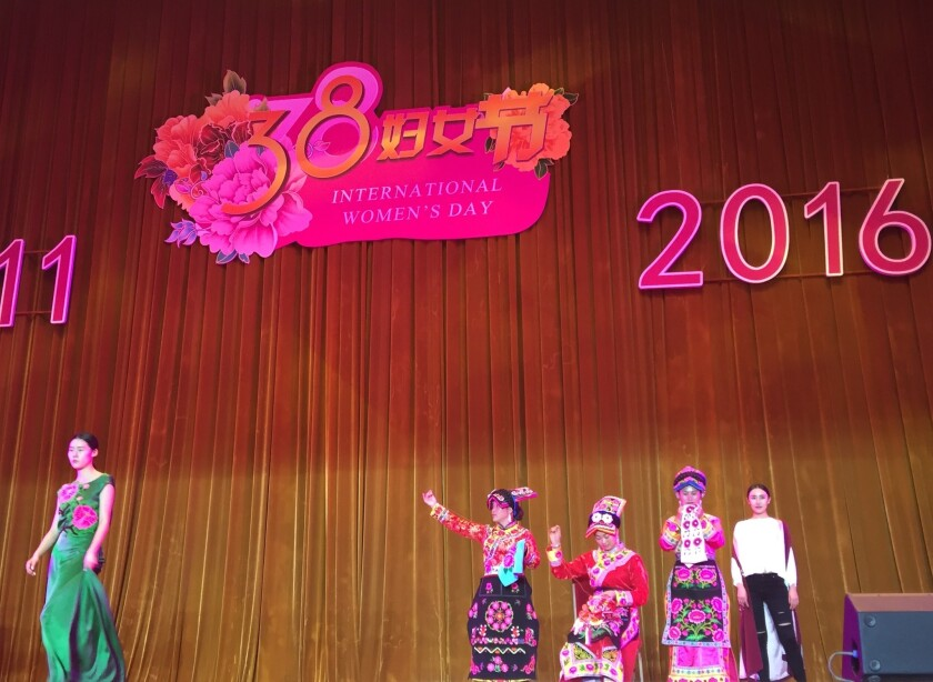 """A model shows off a green dress while women dressed in traditional costumes from one of China's ethnic minorities """"sew"""" onstage at a reception marking International Women's Day in Beijing."""